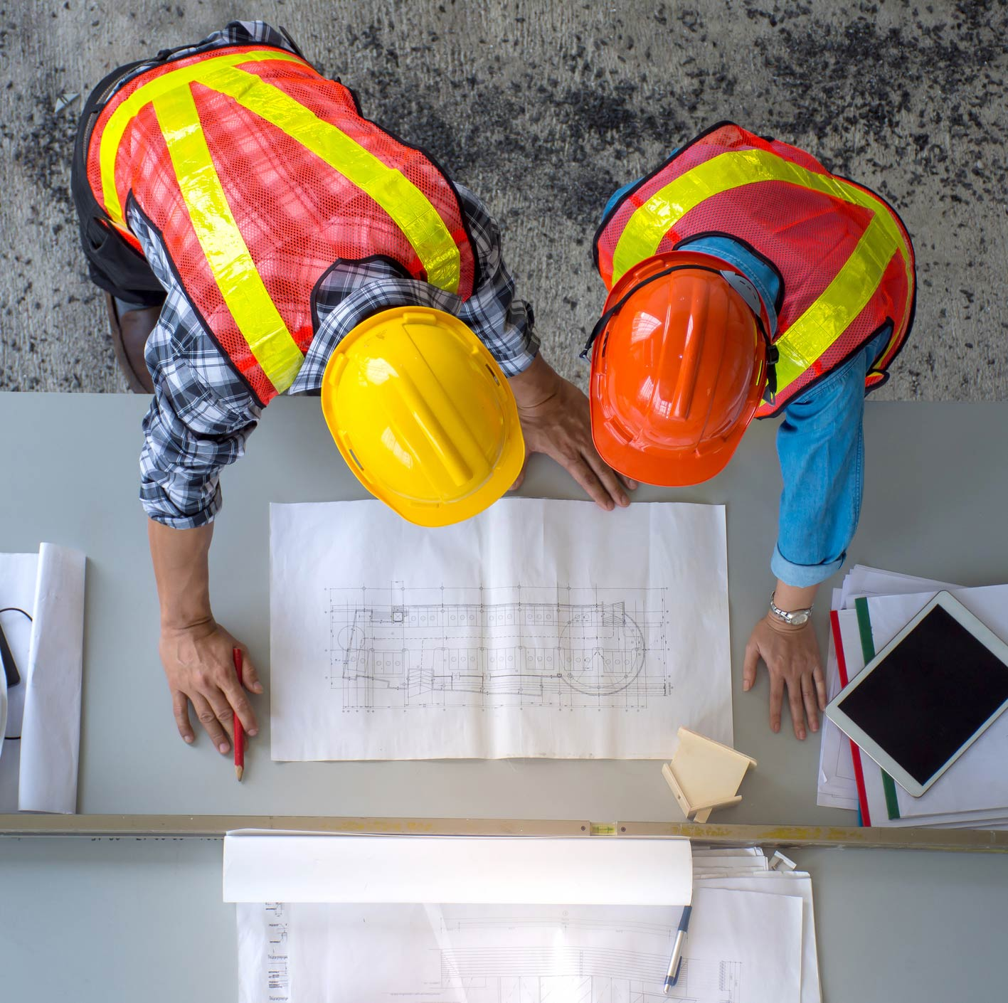 Construction safety. Two men with hard hats looking at blueprints.