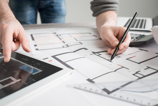 person with tablet and pen looking at design plans
