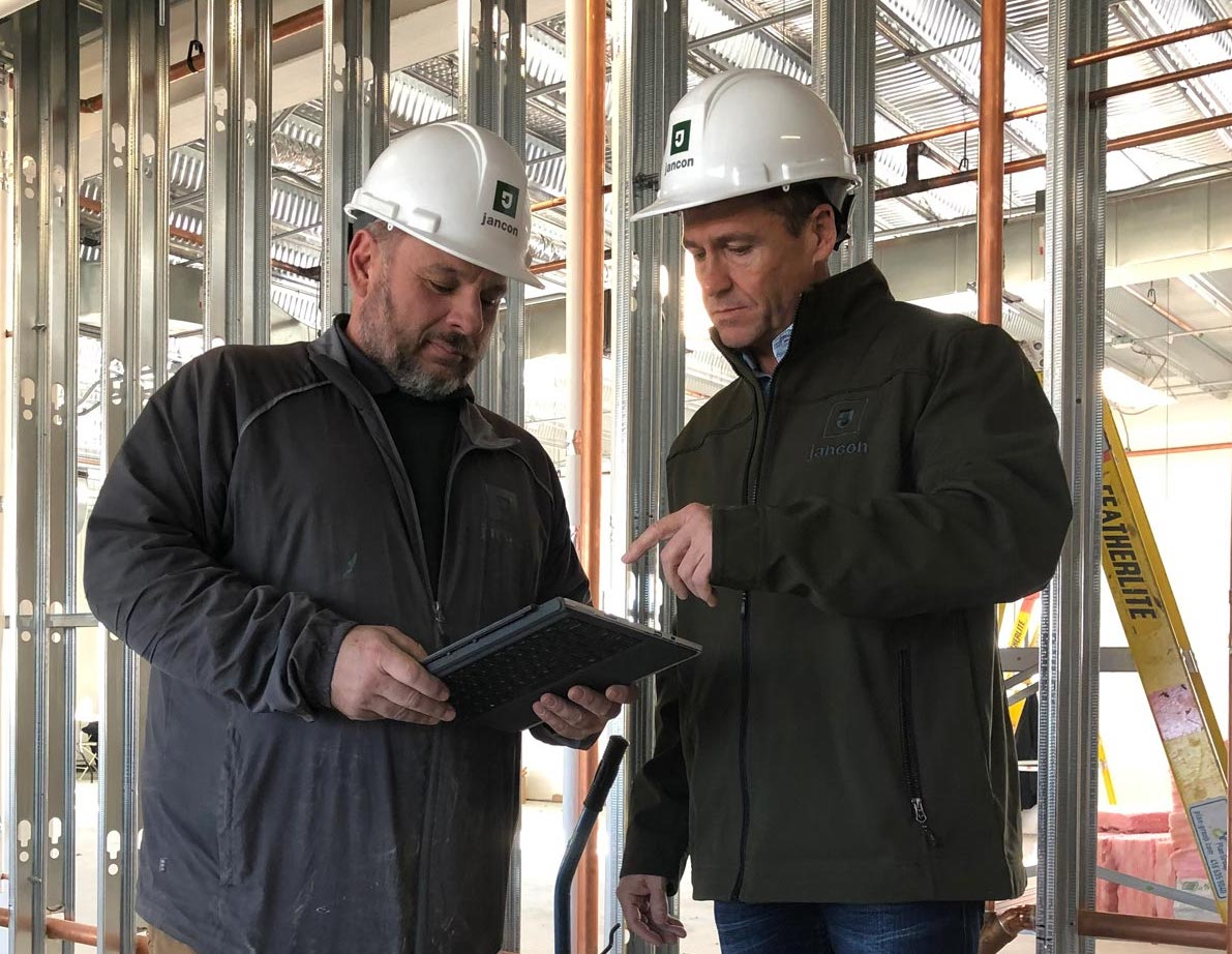 Two men wearing Jancon Construction hard hats discussing building services.